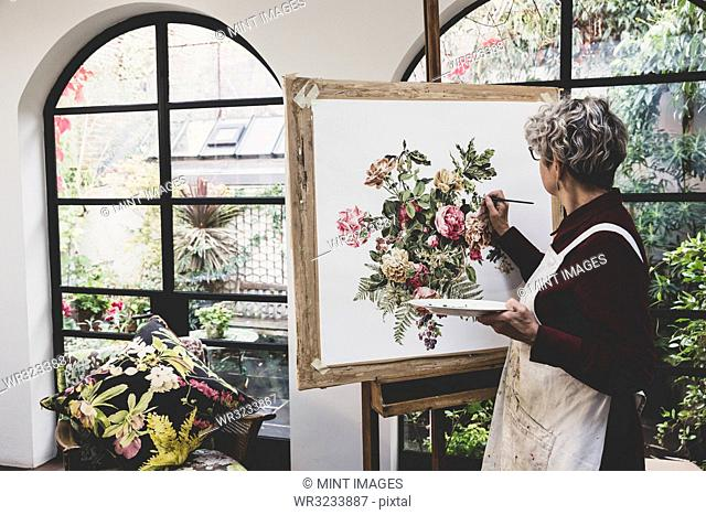 Senior woman wearing glasses, red dress and white apron standing in studio, working on painting of pink tea roses, leaves, berries and other flowers