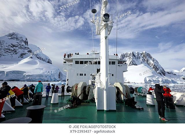 passengers on board ship passing between roullin point and cape cloos at the end of the lemaire channel antarctica
