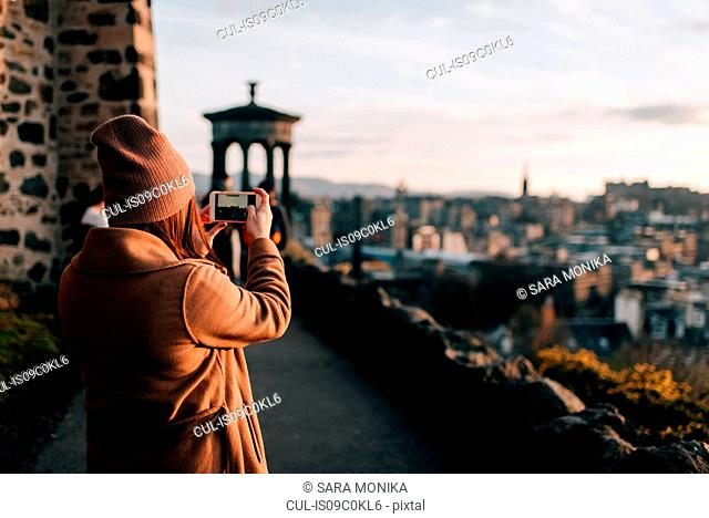 Woman taking photo from Calton Hill, Edinburgh, Scotland