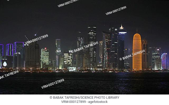 Timelapse of the skyline of Doha, Qatar, at night. At right is the Doha tower (orange). The Persian Gulf is in the foreground