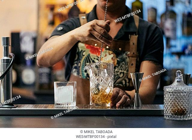 Bartender mixing cocktail in a bar