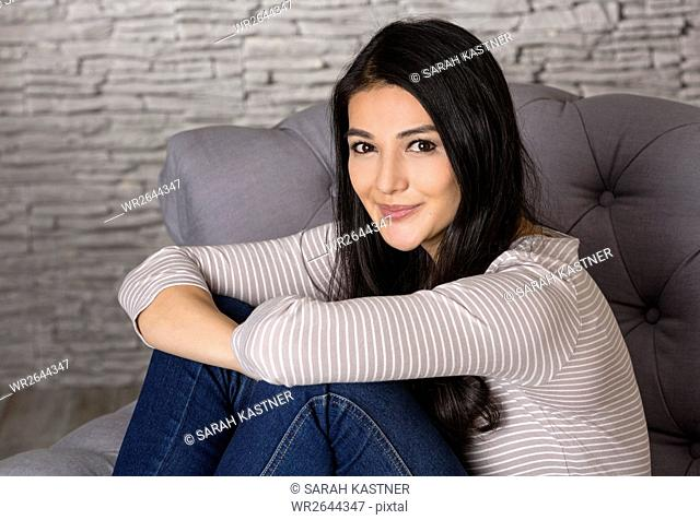 Woman sitting on an armchair
