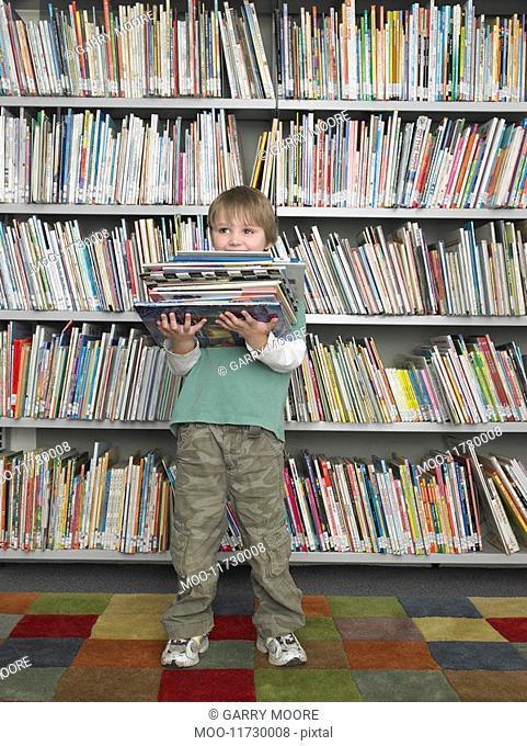 Boy holding stack of books in front of library bookshelf