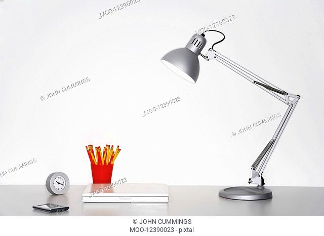 Angle poise lamp laptop clock pencils and PDA on desk