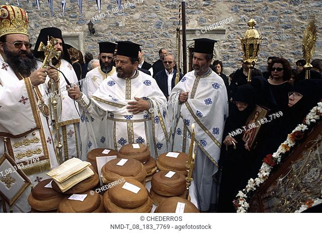 Priests making a religious offering in front of a picture, Crete, Greece