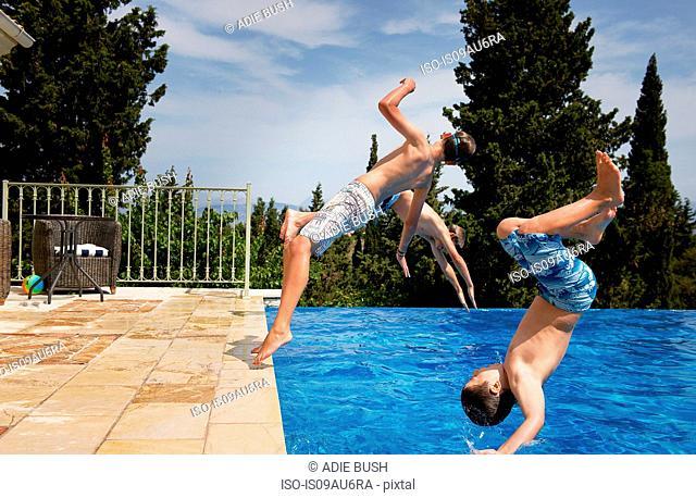 Three boys diving backward into apartment swimming pool