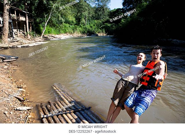 Young tourists bamboo rafting down the river; Chiang Mai, Thailand