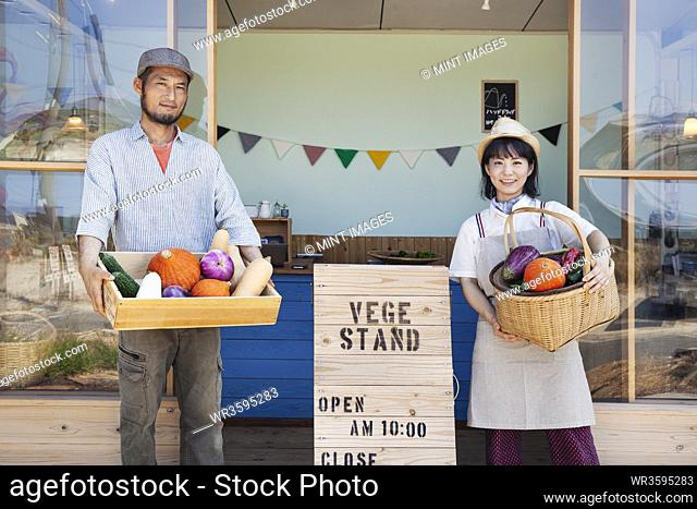 Japanese man and woman standing outside a farm shop, holding crate and basket with fresh vegetables, looking at camera