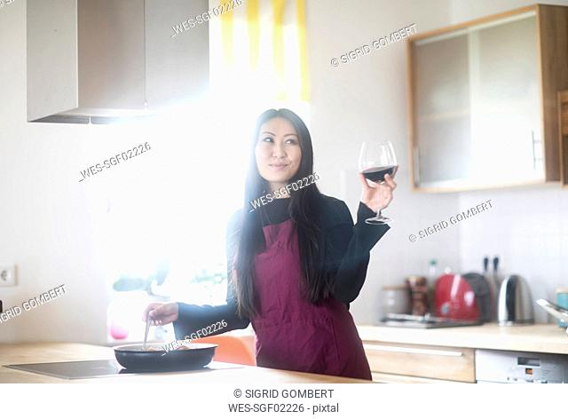 Young woman cooking at home holding glass of red wine