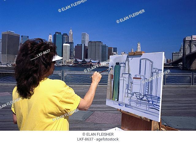 Woman on Brooklyn Bridge painting high rise buildings, Manhattan, New York, USA, America