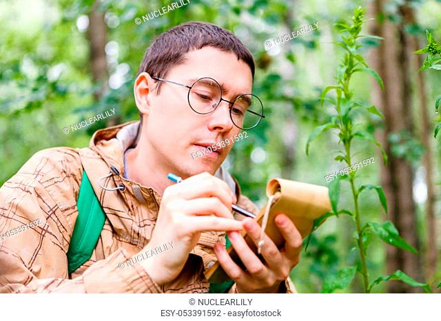 Picture of dark-haired biologist with glasses writing with pencil in notebook at forest among plants and trees in summer afternoon