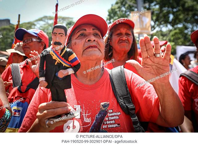 20 May 2019, Venezuela, Caracas: A supporter of Venezuelan President Nicolas Maduro is wearing a Maduro doll at a rally marking the anniversary of his...
