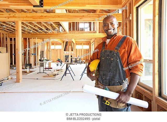 Black construction worker holding blueprints in unfinished room