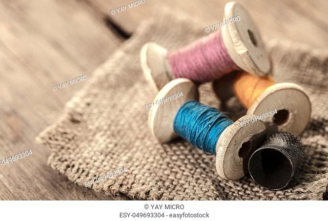 spool of threads and thimble on a wooden background