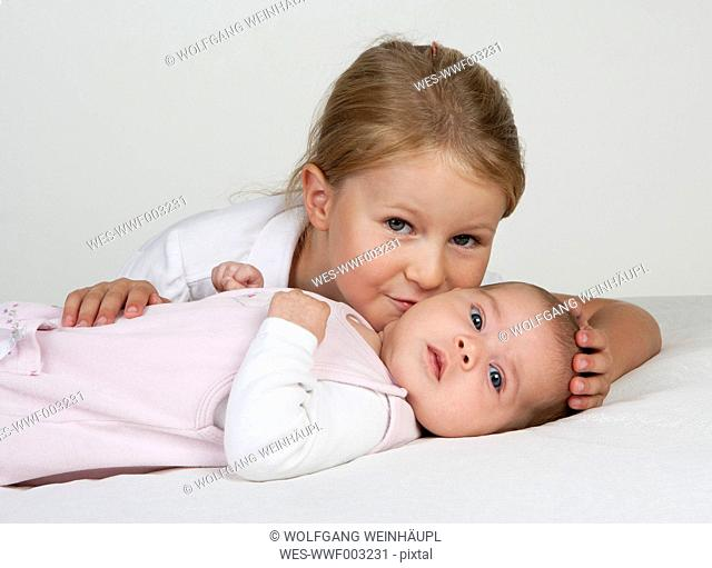 Portrait of little girl kissing newborn sister