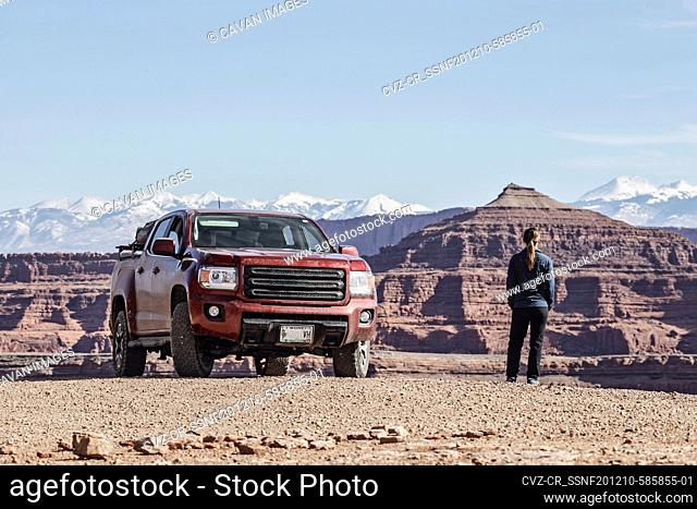woman stands next to dirty off road red pickup truck near Moab Utah