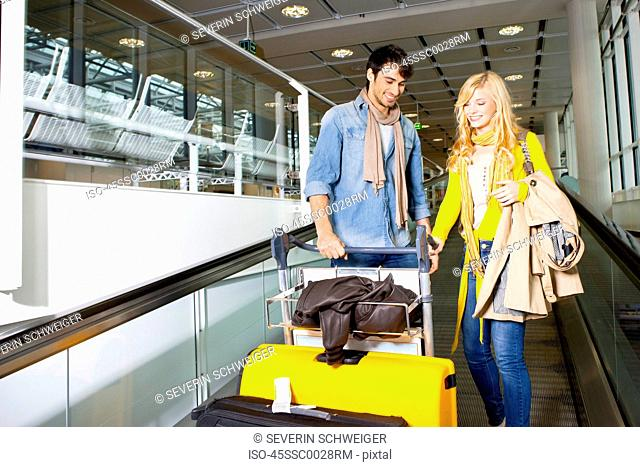 Couple on moving walkway in airport