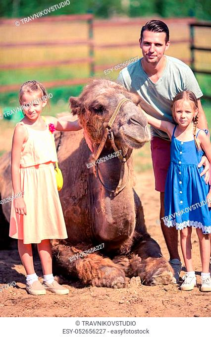 Family with camels in the zoo on warm and sunny summer day. Children watching zoo animals standing by the fence. Active family leisure