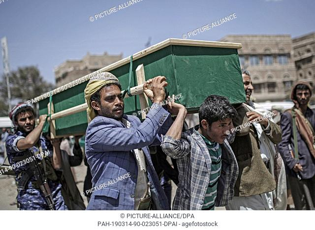 14 March 2019, Yemen, Sanaa: Mourners carry the coffins of victims of an airstrike by the Saudi-led coalition during a funeral procession