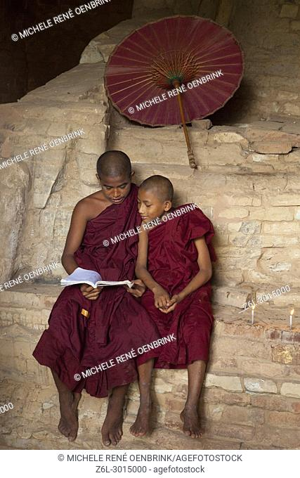 Young monk boy teaching in traditional robes at a temple in Bagan Myanmar