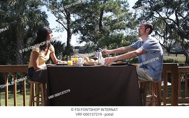 MS, Lockdown of a man pouring coffee for his girlfriend at breakfast, outdoors
