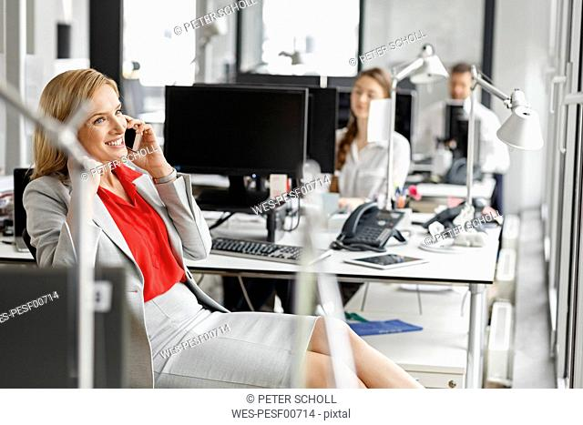Businesswoman at desk in office on cell phone