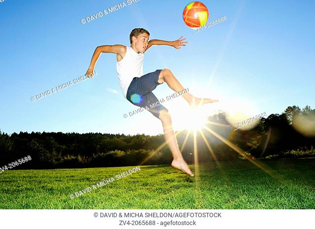 Young boy playing soccer on a meadow, Germany