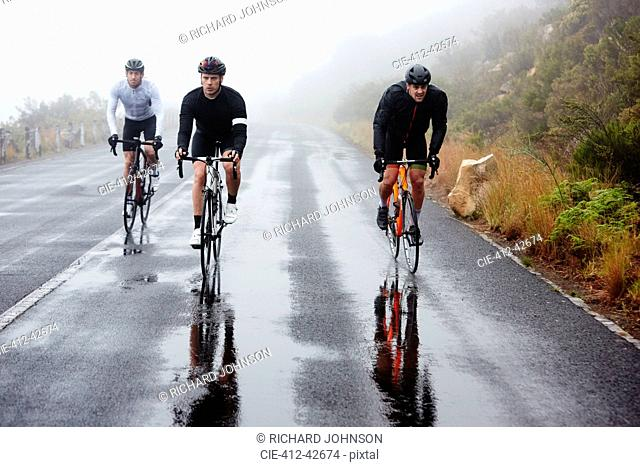 Male cyclists cycling on wet road