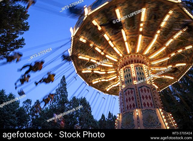 Flying chairs in the amusement park illuminated at dusk, MADRID, SPAIN, EUROPE