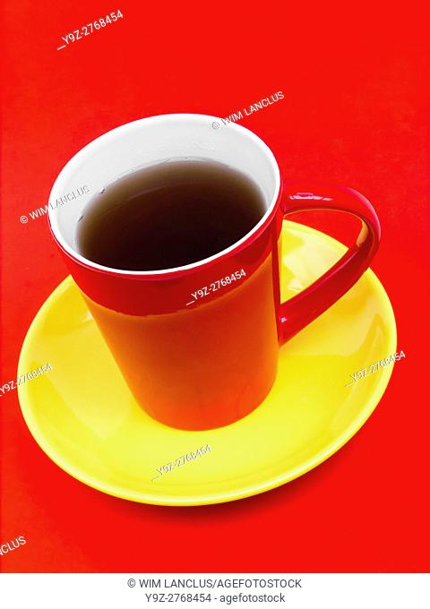 Coffee in red cup on yellow saucer against red background, colors representing spanish flag
