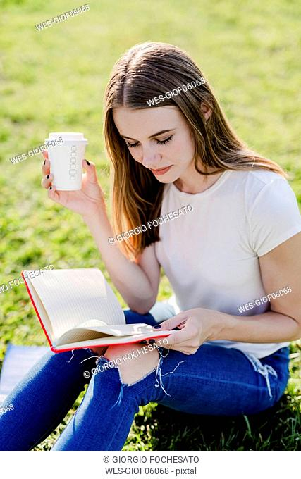 Young woman exploring New York City, taking a break, reading book