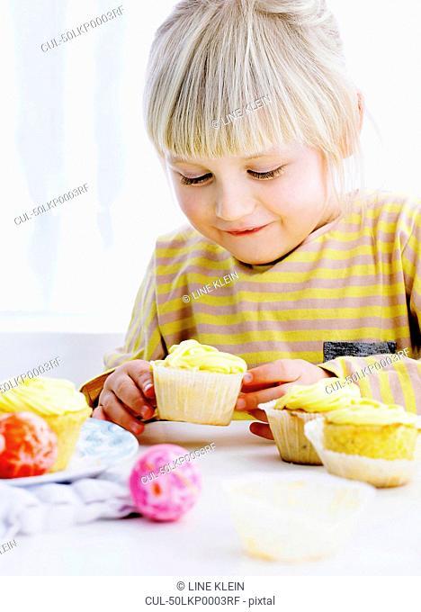 Smiling girl admiring cupcake