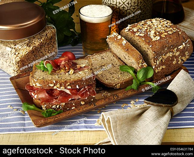 homemade ham and tomato wholemeal bread sandwich with glass of beer in wood table