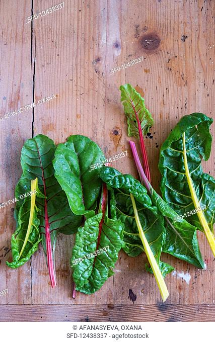 Swiss chard with stalks of various colours on wooden surface