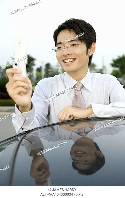 Young businessman leaning against car, holding up cell phone, smiling