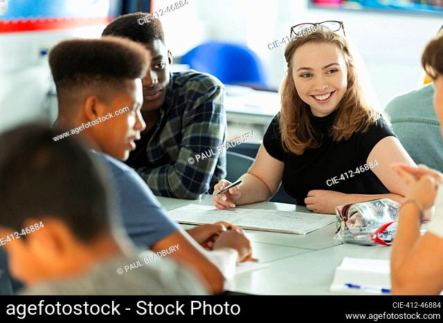 Smiling high school girl student talking with classmates in classroom