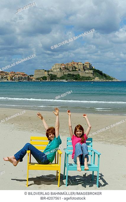 Children sitting in colorful beach chairs on the beach of Calvi, Haute-Corse, Corsica, France