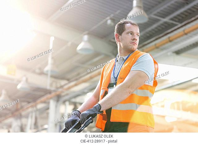 Worker in protective workwear pulling pallet truck in factory