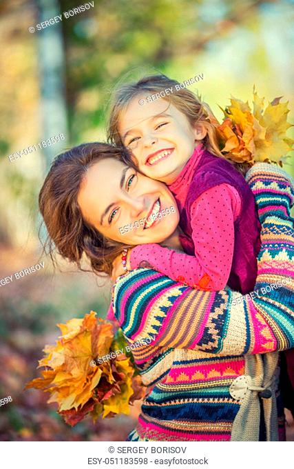 Little girl and her mother enjoy sunny weather in the autumn park