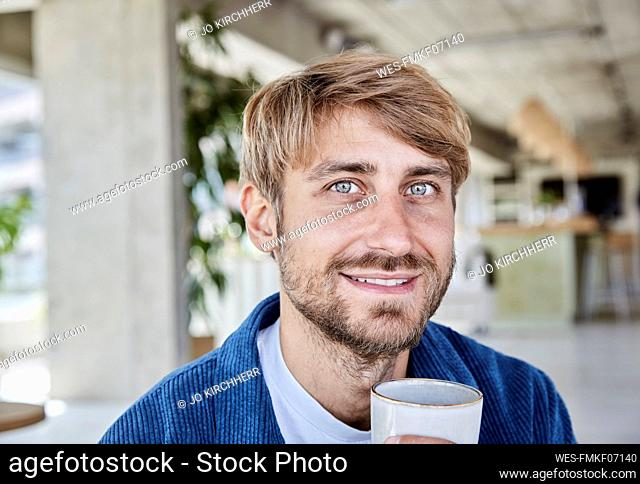 Gray eyed man having coffee at loft