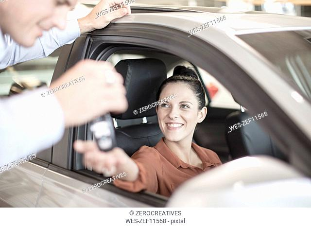 Car dealer handing over key to woman at car dealership