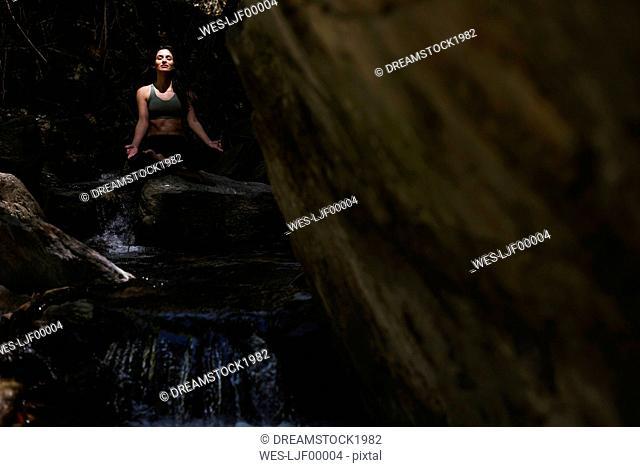 Woman practicing yoga at a brook