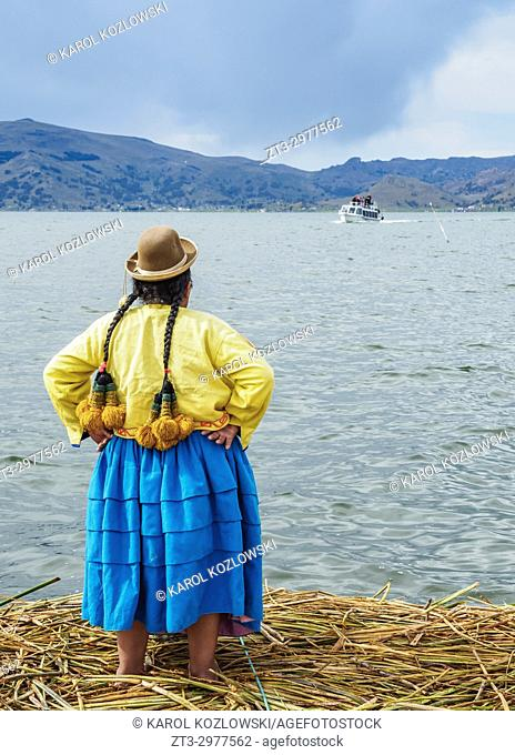Native Uro Lady waiting for the boat with tourists, Uros Floating Islands, Lake Titicaca, Puno Region, Peru