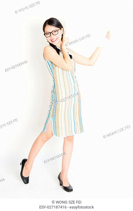 Portrait of young Asian girl in traditional qipao dress hand holding a white blank paper card, celebrating Chinese Lunar New Year or spring festival