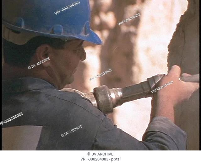 A construction worker drills holes