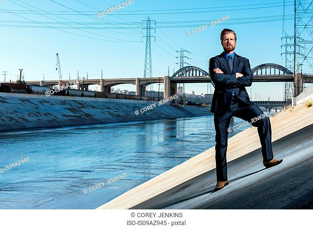 Businessman arms crossed, looking at camera, Los Angeles river, California, USA