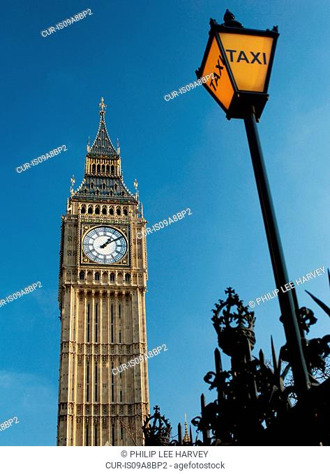 An old fashioned taxi rank sign beside Big Ben and the Houses of Parliament, London, UK