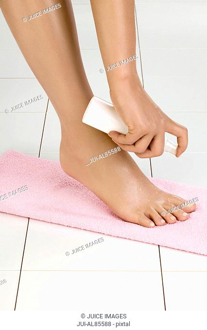 Close up of woman spraying beauty treatment on bare foot