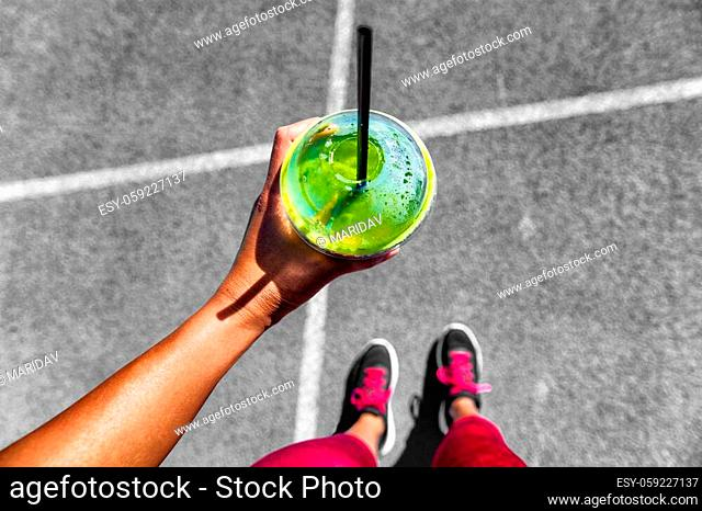 Green smoothie woman drinking plastic cup breakfast meal takeaway to go after morning run on city streets. Healthy lifestyle sporty person pov of hand holding...