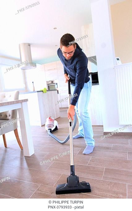 France, young man using vacuum cleaner